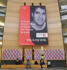 "The University's $6million ""this is my time"" promotion campaign is here contrasted with the 2014 York Federation of Students' 2014 ""#thisismydebt"" effort to protest tuition fee increases. The small poster displace list the student debts of individual students. University staff quickly removed them."
