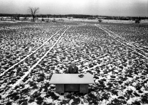 President Murray Ross seated at his desk on the muddy farm field where York University campus is now located. Photo courtesy of York University Libraries, Clara Thomas Archives and Special Collection (?), ASC01639. NEED F#