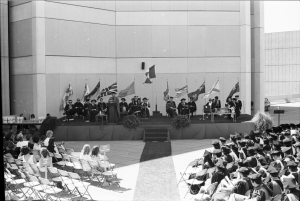Hold on to your hats! Convocations were often windy affairs on the Ross Terrace. The photo is showing the convocation podium against the wall of the Scott Library. Photo courtesy of York University Libraries, Clara Thomas Archives and Special Collection, ASC19502.