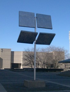 """George Rickey's """"Four Squares in a Square"""" on a warm summer day. The trees in the Central Square Garden and the Curtis Lecture Halls are seen in the background. Photo courtesy the author."""